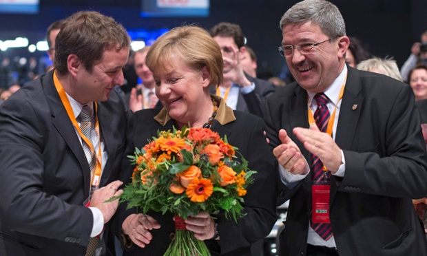 German Chancellor and chairwoman of the Christian Democratic Party, CDU, Angela Merkel reacts while holding a bunch of flowers as the result of her reelection as party leader was announced at the party's 2012 convention in Hannover, Tuesday, Dec. 4, 2012.