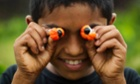 Eye eye: a boy plays with the fruit of the guarana plant at a farm in Maues in the Brazilian Amazon. The town is nicknamed the Land of Guarana after the plant whose seed is used to make the famous guarana soft drink and is an effective stimulant, twice that of coffee. In the language of the Guarani Indians, guarana means 'fruit like the eyes of the people'.