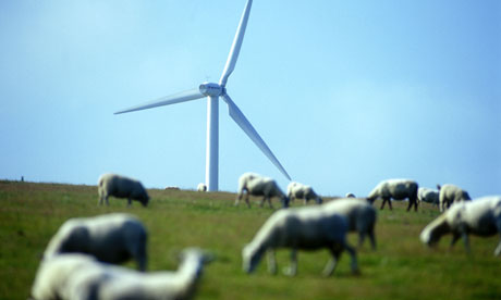 A wind turbine towers over grazing sheep in South Wales