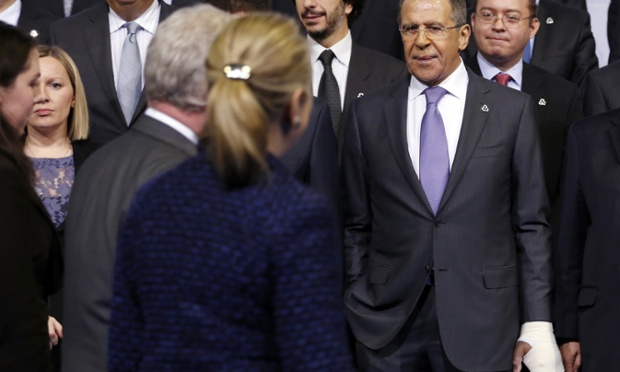Russian foreign minister Sergei Lavrov watches as  US Secretary of State Hillary Clinton arrives for a group photo at the OSCE conference in Dublin.