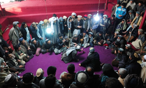 Afghan spectators watch a quail fight in Mazar-i Sharif.  A popular sport in Afghanistan, two birds are placed inside a circle and made to fight each other until any one of the bird runs out of the circle and the bird that stays is declared the winner. Bird fighting was not allowed during the years of rule by the Taliban regime.