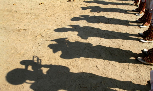 Shadows of Indian members of a band are seen as they play for Indian holy men during a ceremony to worship the land allotted to them for setting up their tents for the upcoming Mahakumbh fair in Allahabad.