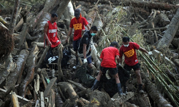 Rescue workers carry bodies of victims of Typhoon Bopha from amongst debris of logs in New Bataan, Philippines