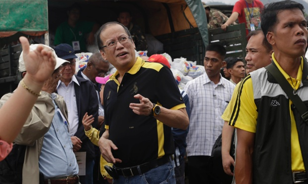 Philippine President Benigno Aquino III talks to local government officials prior to distributing relief goods to victims in Compostela Valley.