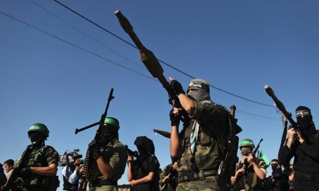 Palestinian members of the al-Qassam brigades stand guard