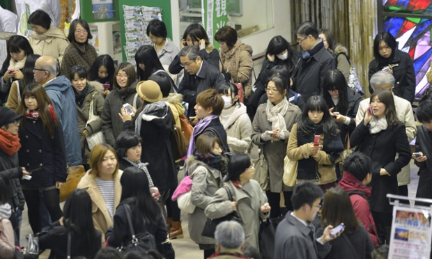 People on their mobile phones as they are stranded at Sendai railway after trains were halted following a strong earthquake that struck off the coast of northeastern Japan. It is the same region that was hit by a massive earthquake and tsunami last year.