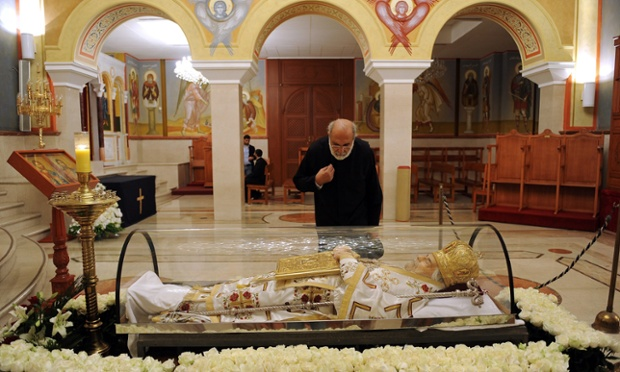 A Lebanese clergyman pays his respects to the body of Orthodox Patriarch of Antioch Ignatius Hazim IV as he lies in state during a mass to pray for his soul at the Saint Nicolas Church in Beirut.