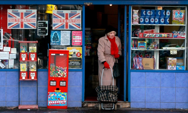 A woman leaves a shop displaying Union flag posters in the window, in the Shankill Road area of West Belfast.