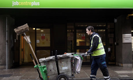 Street cleaner pushes cart past Jobcentreplus building