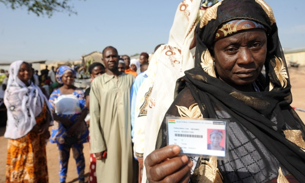 A woman shows her voter's card before voting at Bole polling station in northern Ghana. Ghanaians are voting in a presidential election.