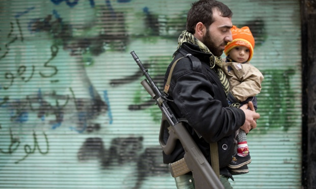 A rebel fighter carries his son after Friday prayers in the al-Fardos neighbourhood of Aleppo.