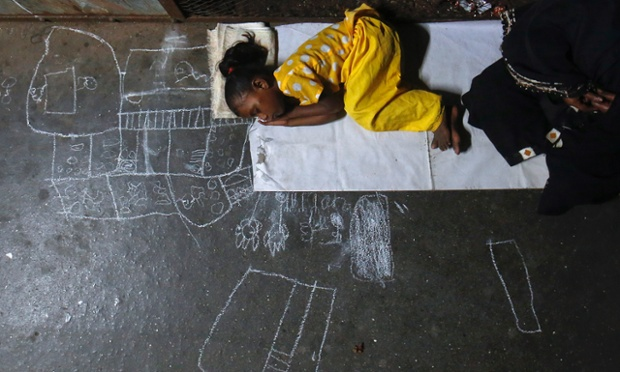 Noor Jahan, 5, sleeps on the chalk drawings she made as her mother begs at a railway station in Mumbai.