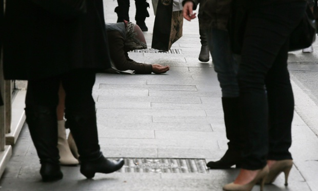 People stroll with their shopping bags past a woman begging for money in downtown Rome.