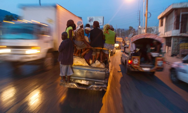 Vendors are transported in a vehicle called a 'tap-tap' through early morning traffic in Port-au-Prince, Haiti