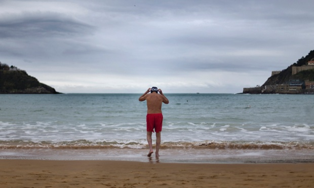 A man prepares to bathe in the Cantabric Sea at La Concha beach in San Sebastian, northern Spain. The air temperature was 9C degrees and the water temperature 13C degrees. He should try the North sea.