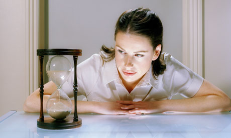 woman looking at hourglass