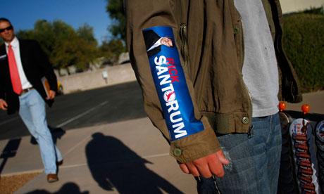 A button vendor wears a campaign sticker for Rick Santorum