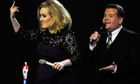 Adele gestures after being interrupted following her awards acceptance speech