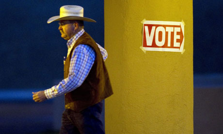 A man wearing a cowboy hat leaves a polling place in Wickenburg, Arizona.