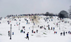 People play in the snow on Primrose Hill in north London