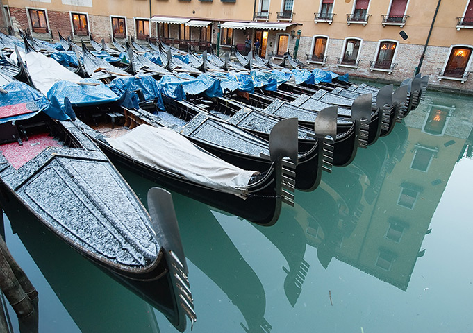 Frozen Venice: Gondolas covered by a snow flurry