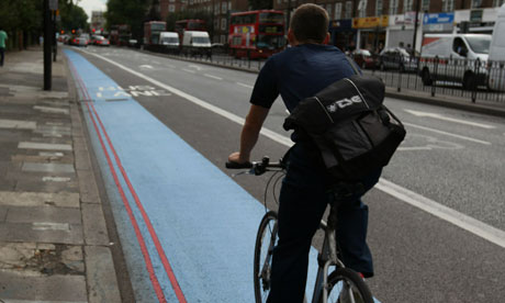 A cyclist on a blue bike lane in west London