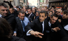 French president, Nicolas Sarkozy, is protected from protesters in Bayonne by police officers