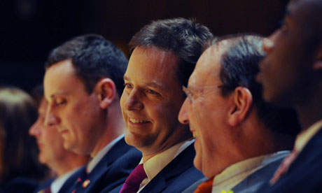 A smiling Nick Clegg sits in the audience at the Lib Dem conference