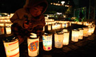Japan disaster anniversary: a boy lights a candle at a memorial service in Koriyama