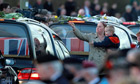 A mourner places a rose on one of the hearses carrying six soldiers killed in Afghanistan