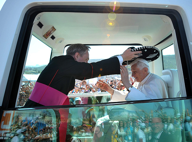 Pope visit to Mexico: Monsignor Georg Gaenswein places a Mexican sombrero on Pope Benedict