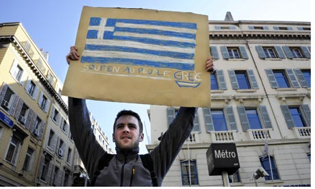 A man holds a placard bearing the Greek