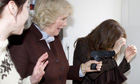 The Duchess of Cornwall holds a prop gun on a visit to the set of The Killing
