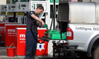 A person fills up fuel containers at a petrol station in Linlithgow as panic-buying spreads