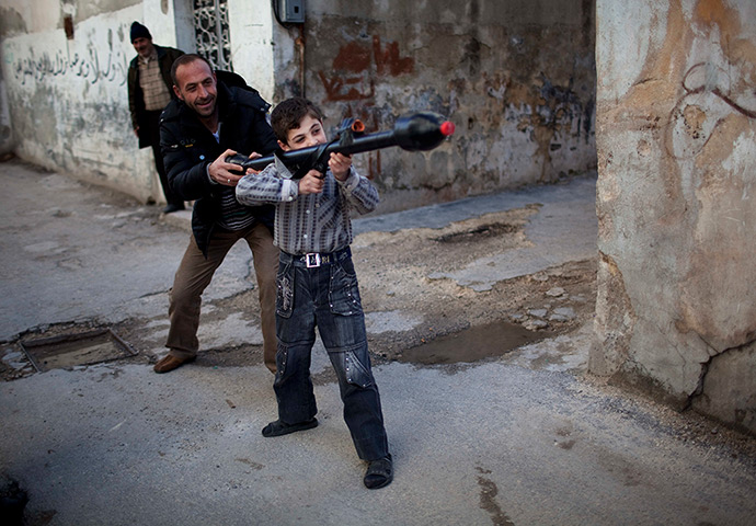 24 hours in pictures: Idlib, Syria: A man teaches a boy how to use a toy rocket propelled grenade
