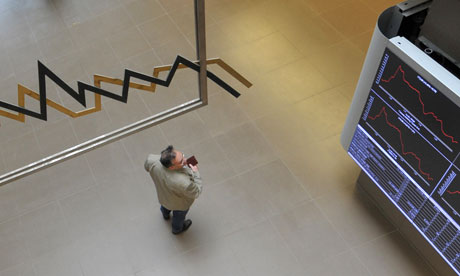 A man watches an index display at the Athens stock exchange