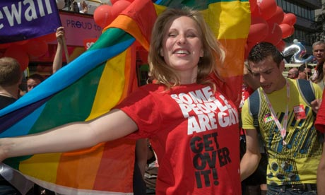 A woman at a Gay Pride march with a T-shirt featuring Stonewall's slogan.