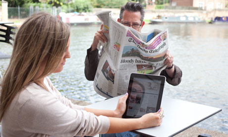 Two people read the Daily Telegraph online and in print