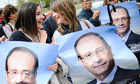 François Hollande supporters hold up posters of the candidate during a campaign visit