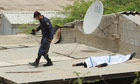 A policeman next to what is believed to be the body of a protester on a roof in Shakhura, Bahrain