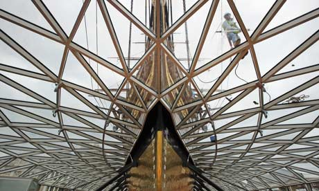 A workman cleans the glass canopy surrounding the newly refurbished Cutty Sark