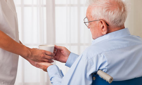 Nurse giving beverage to elderly man in a wheelchair care home residential care