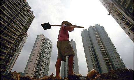 A Chinese manual worker surrounded by skyscrapers in Suining