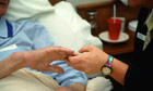 Hospice worker holding the hand of a patient