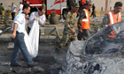 Syrians remove the remains of victims of the car suicide car bombings in Damascus