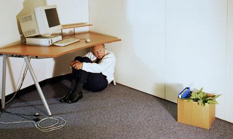 Mature businessman sitting under desk
