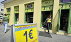A woman exits a one euro shop in central Athens