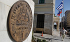 A man walks towards a replica of a drachma coin outside Athens town hall in Greece