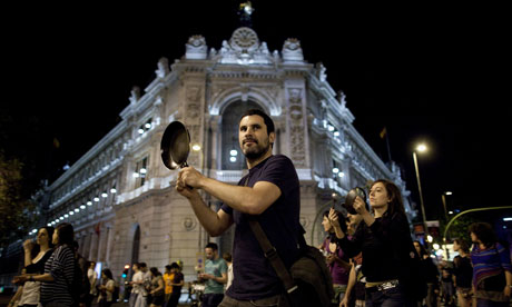 A protester hits a pot while walking past the Bank of Spain in Madrid