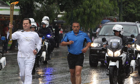 A torchbearer runs with the Olympic flame in front of the Greek parliament in Athens on 17 May 2012.